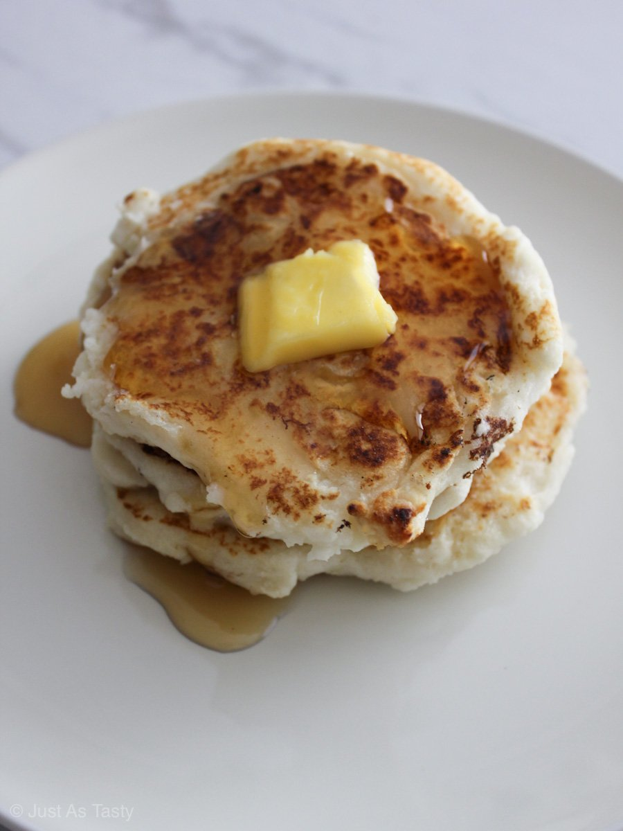 Stack of gluten free pancakes with butter and syrup.