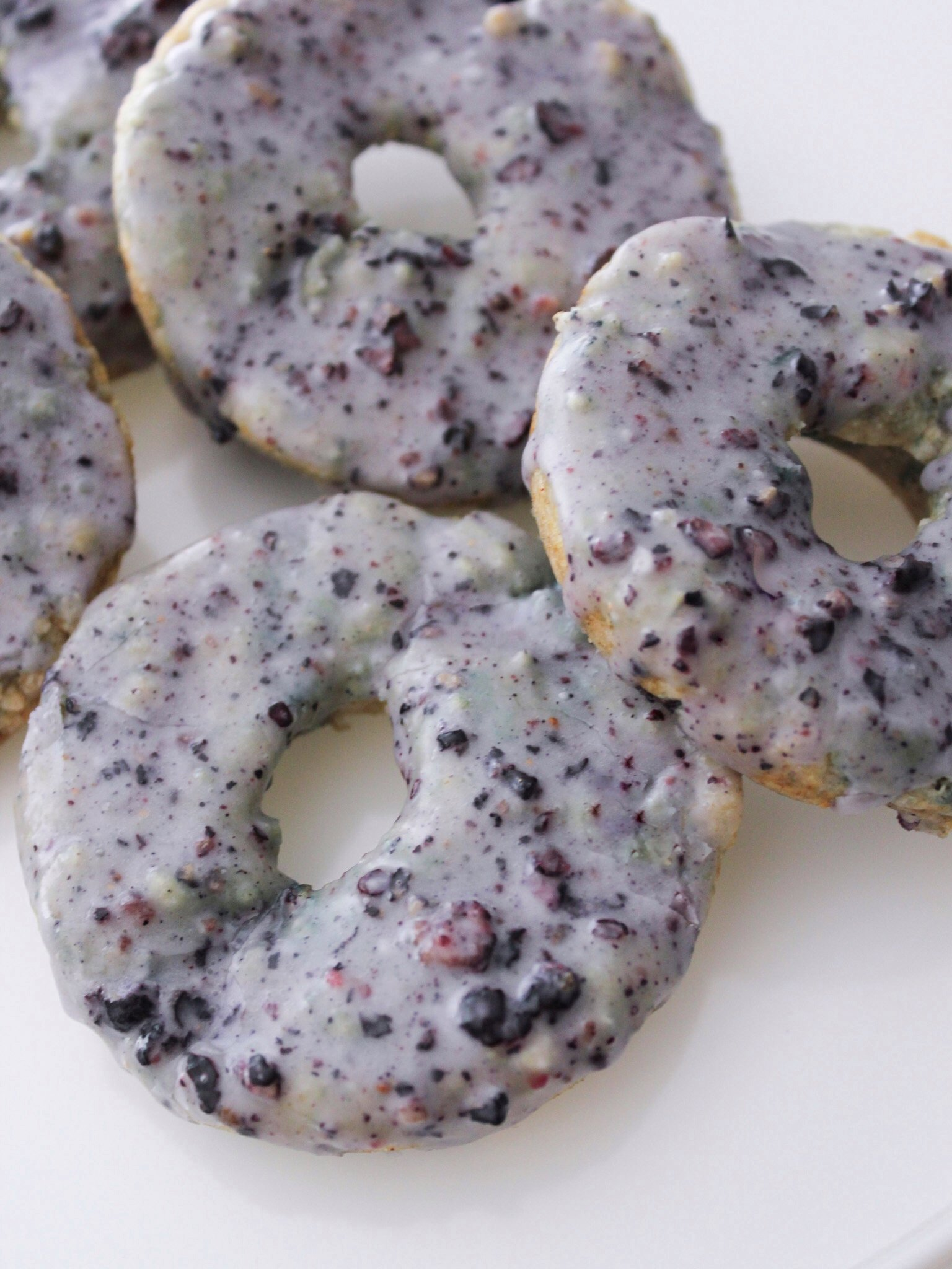 Blueberry donuts on a white plate with a purple glaze.