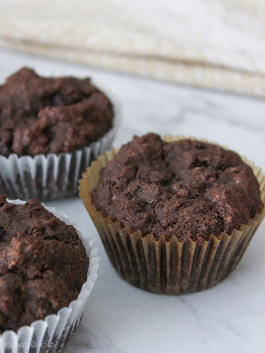 Gluten free chocolate muffins on a white marble surface.