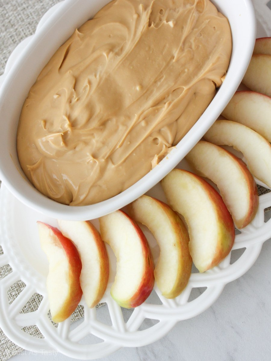 Caramel apple dip in a white bowl surrounded by apple slices.