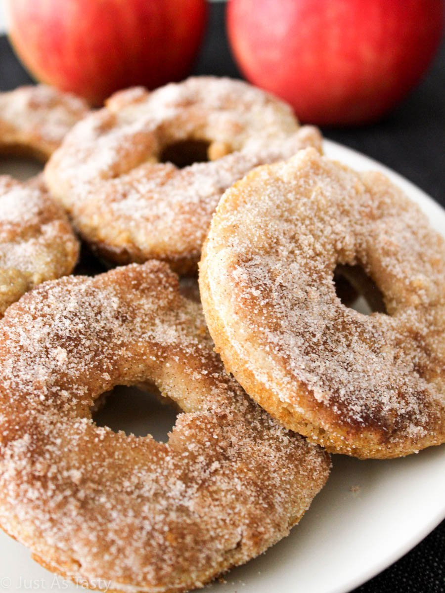 Gluten free apple cider donuts coated in cinnamon sugar on a white plate.