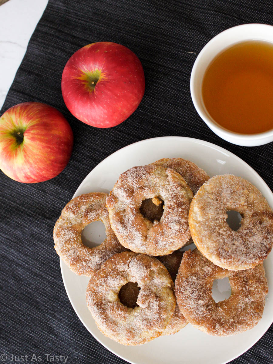 Baked apple cider donuts covered in cinnamon sugar on a white plate.