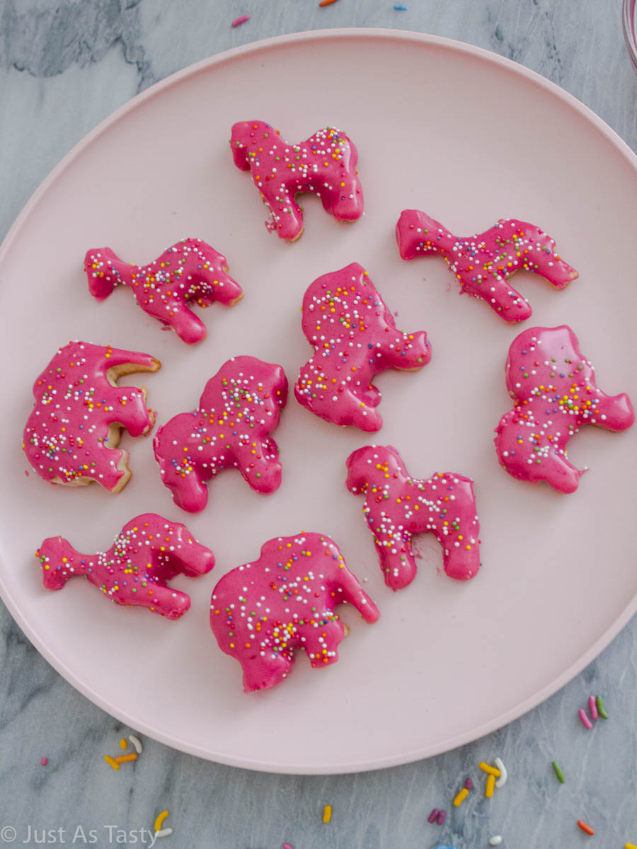 Pink circus animal cookies topped with sprinkles on a pink plate.