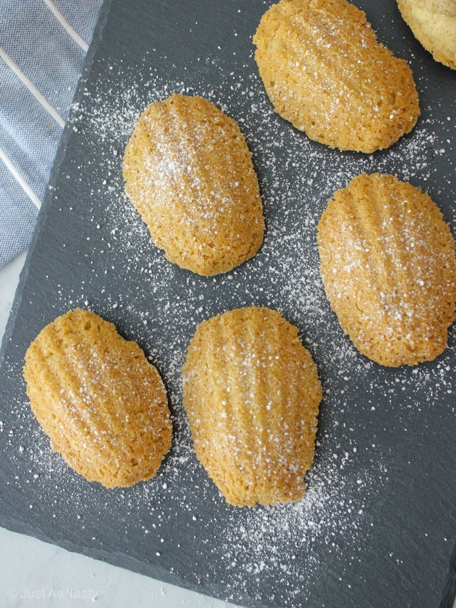 Eggless madeleines dusted with powdered sugar on a grey surface.
