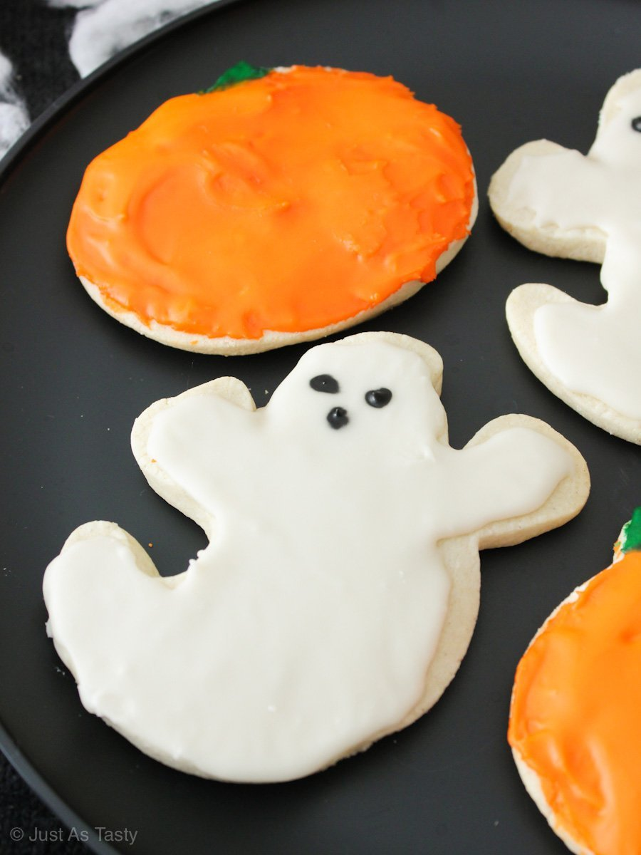 Close-up of frosted ghost and pumpkin shaped Halloween sugar cookies on a black plate.