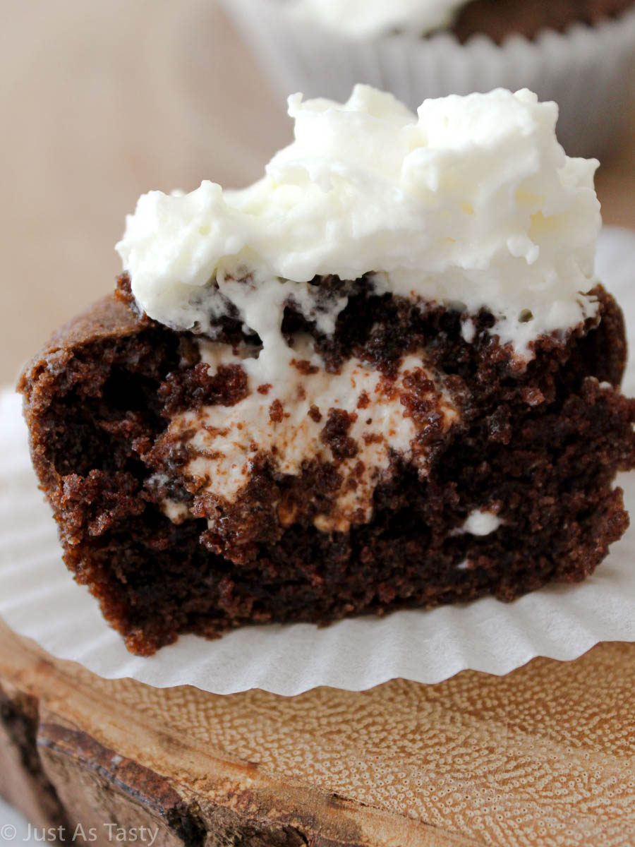 Close-up of sliced hot cocoa cupcake with marshmallow filling inside.