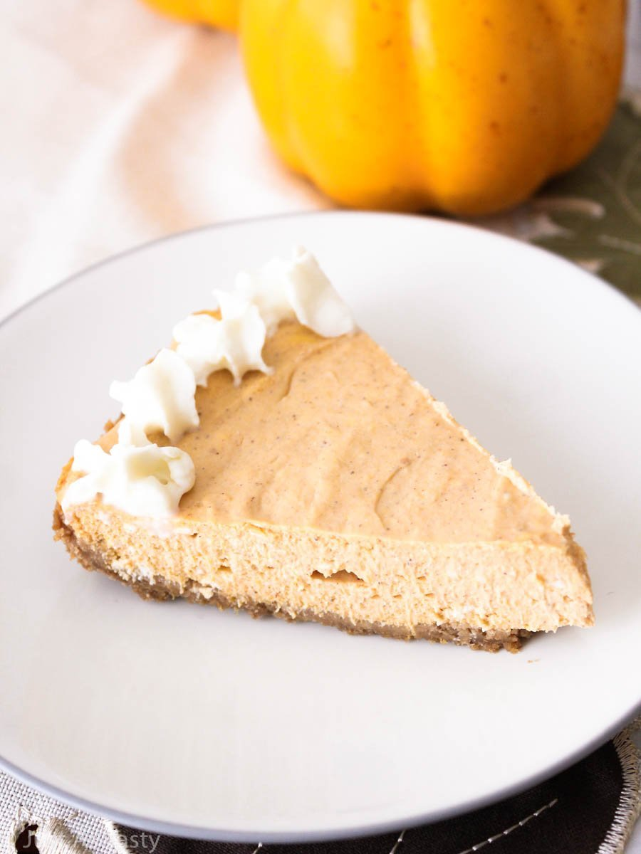 Slice of pumpkin cheesecake on a white plate.