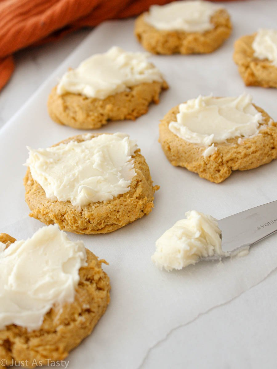 Soft pumpkin cookies with cream cheese frosting on a white surface.