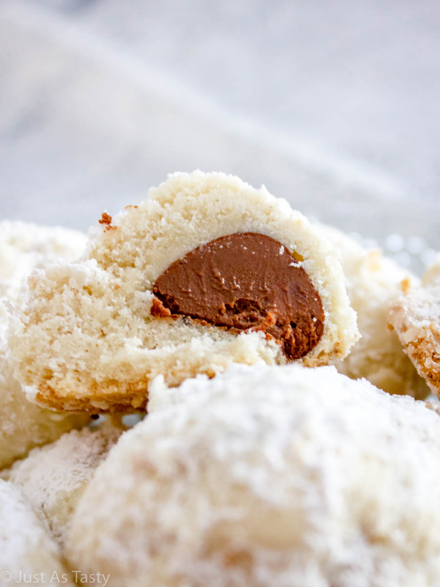 Close-up of chocolate snowball cookies sliced in half to reveal Hershey's Kiss chocolate inside.