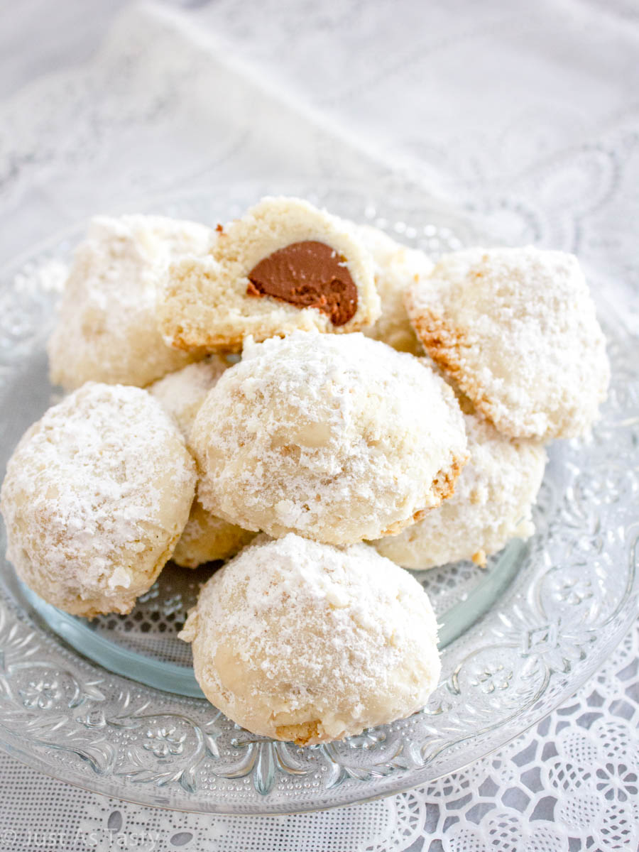 Chocolate snowball cookies on a glass plate.
