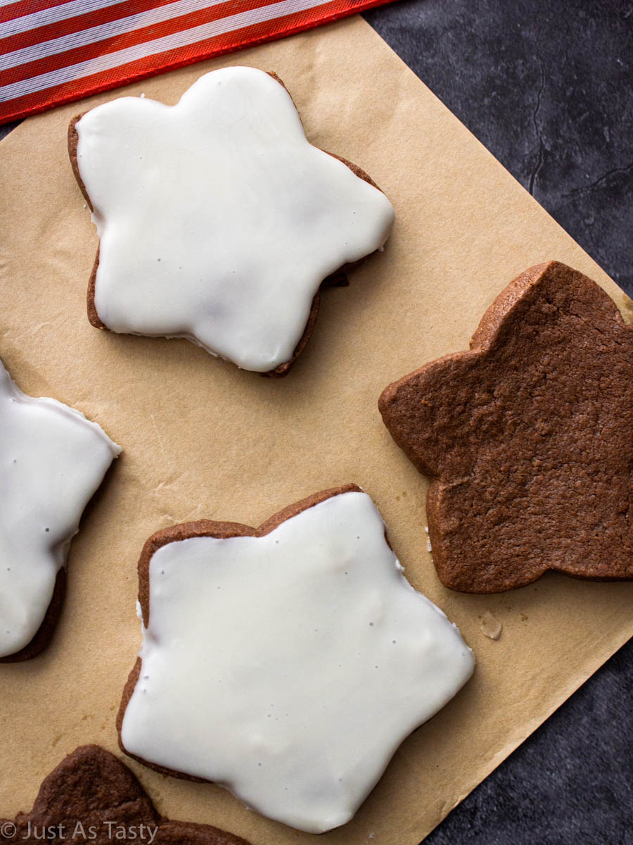 Close-up of star-shaped chocolate sugar cookies on parchment paper.