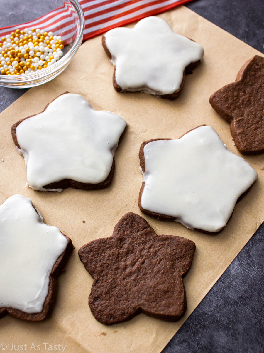 Star-shaped chocolate sugar cookies on brown parchment paper.