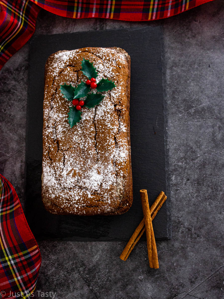 Gluten free gingerbread loaf topped with powdered sugar on a grey surface.