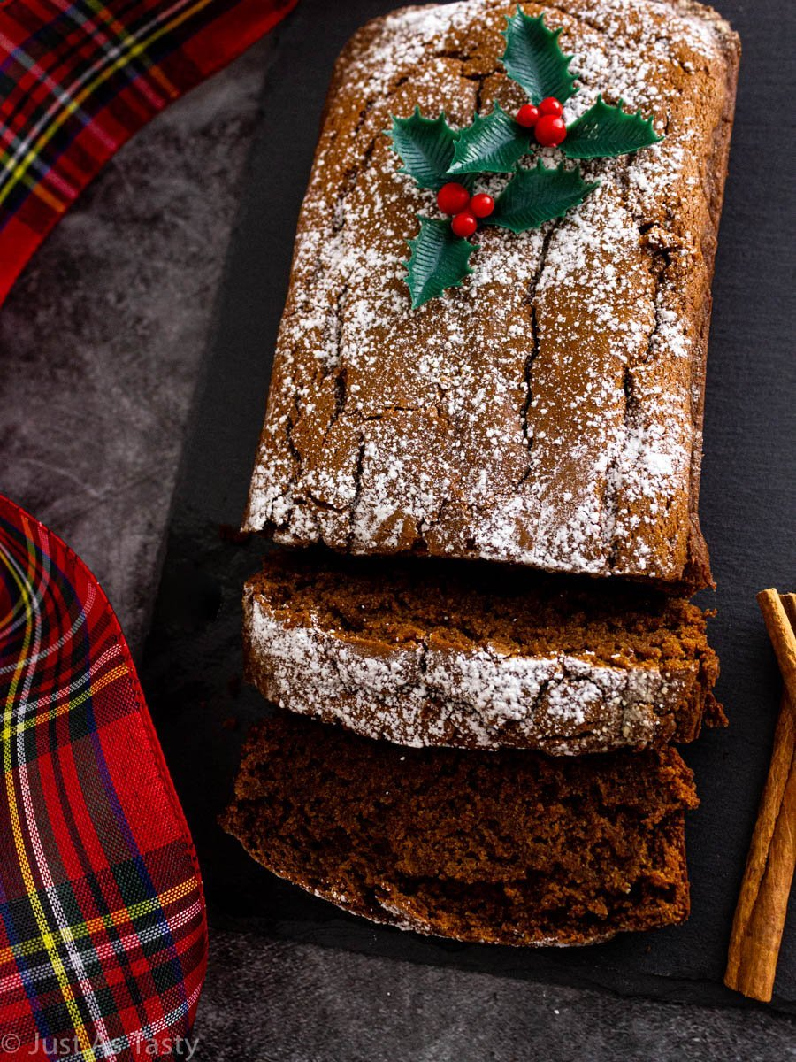 Sliced gluten free gingerbread loaf on a grey surface.