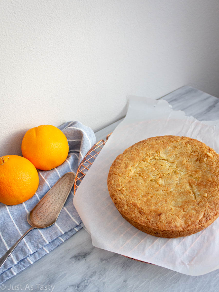 Round orange olive oil cake on a table with oranges.