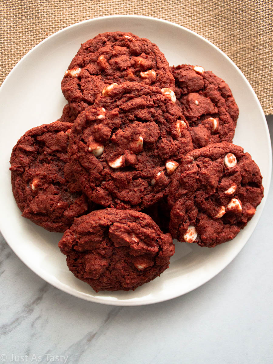 Red velvet cookies with white chocolate chips on a white plate.