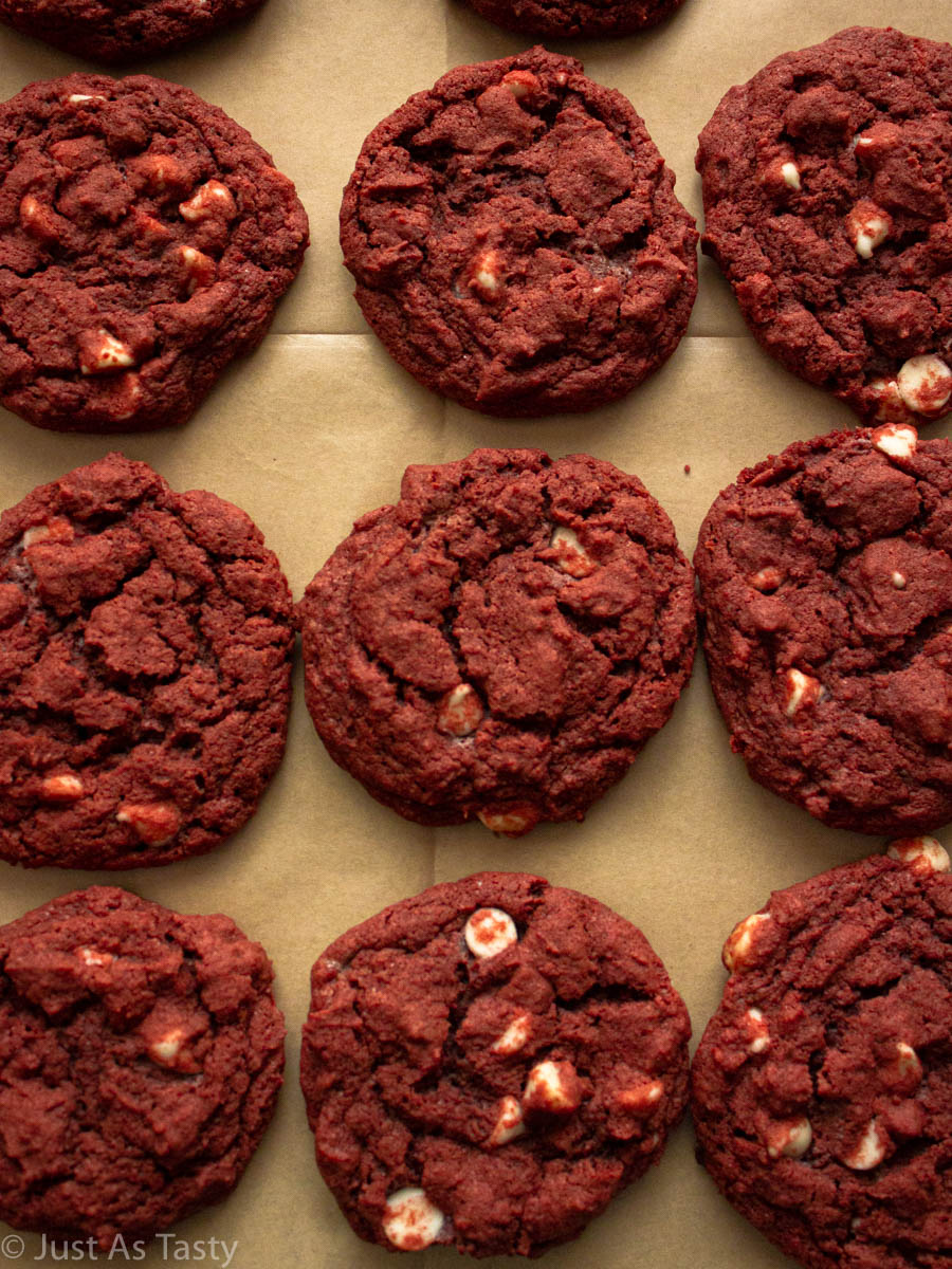 Gluten free red velvet cookies with white chocolate chips lined up on parchment paper.