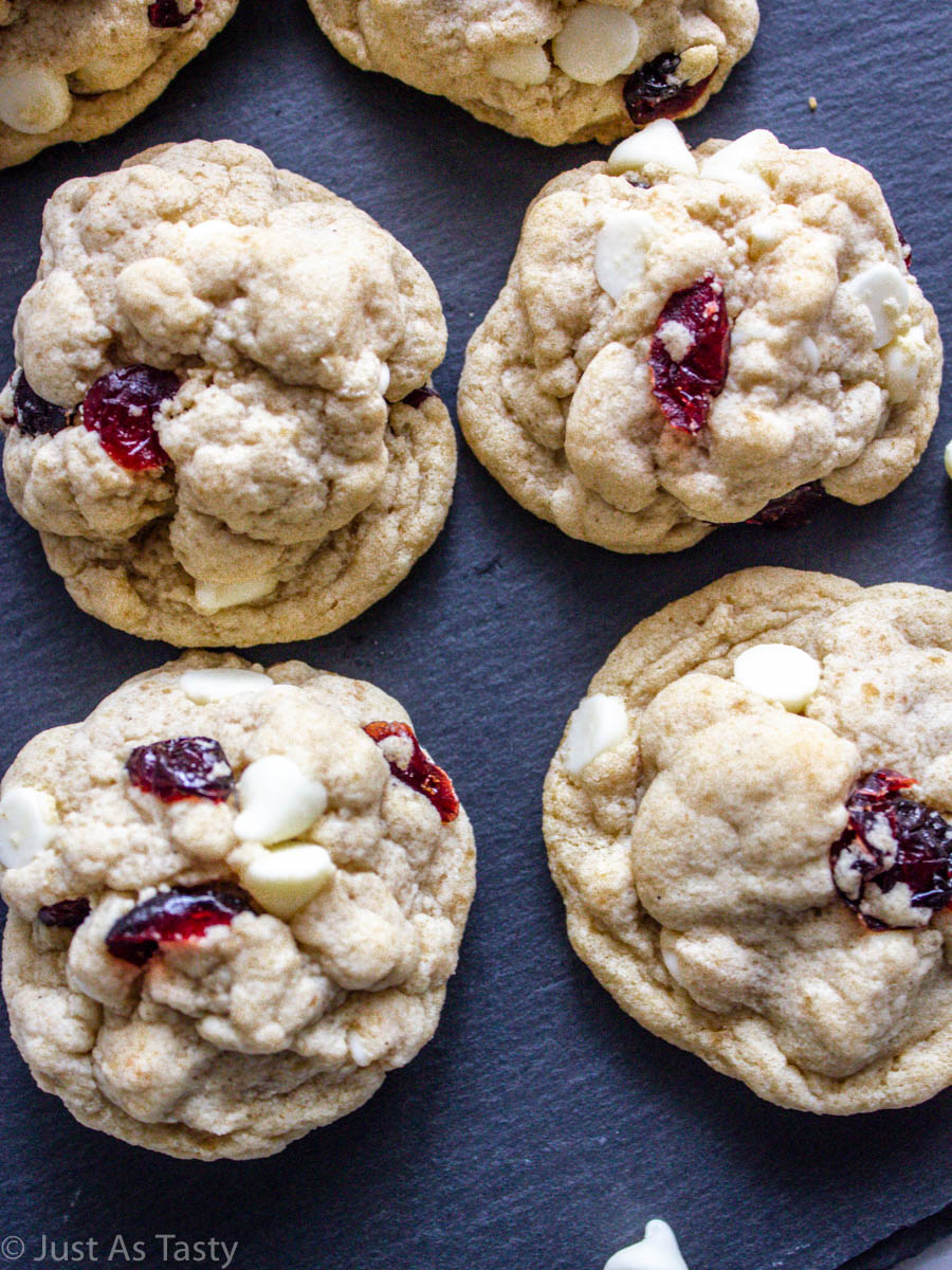 Close-up of white chocolate cranberry cookies on a grey surface.