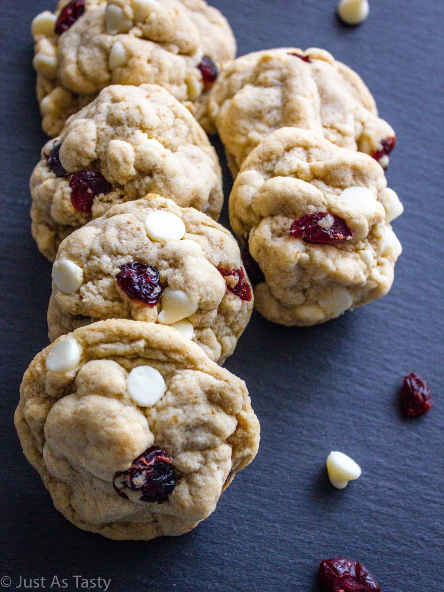 White chocolate cranberry cookies on a grey surface.