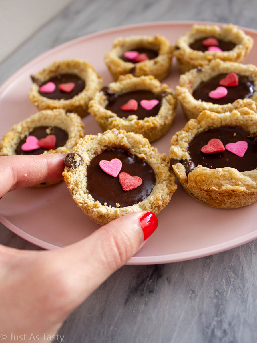 Chocolate chip cookies filled with ganache on a pink plate.