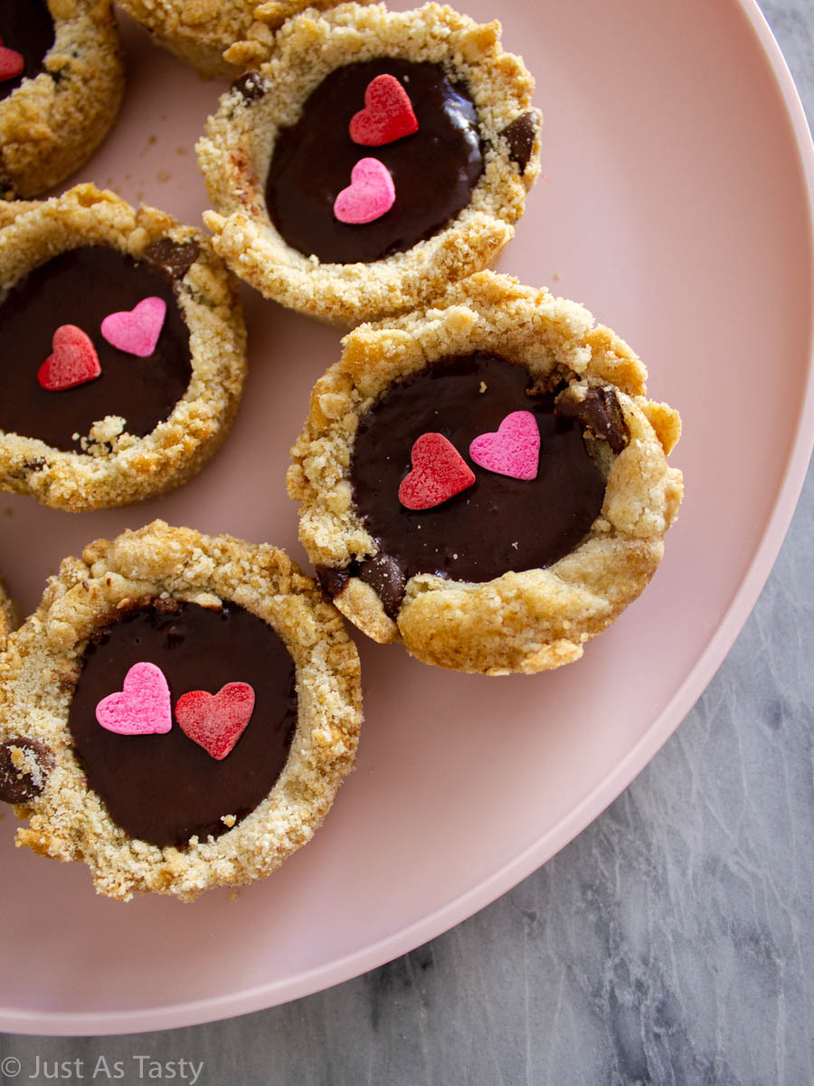 Chocolate chip cookie cups filled with chocolate ganache and topped with heart sprinkles.