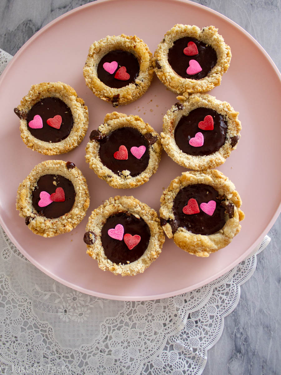 Chocolate chip cookie cups filled with chocolate ganache on a pink plate.