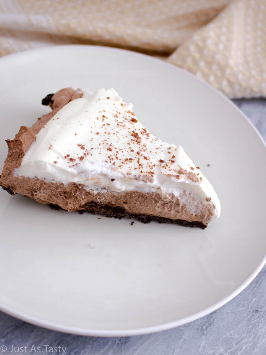 Slice of no bake chocolate mousse pie without eggs on a white plate.