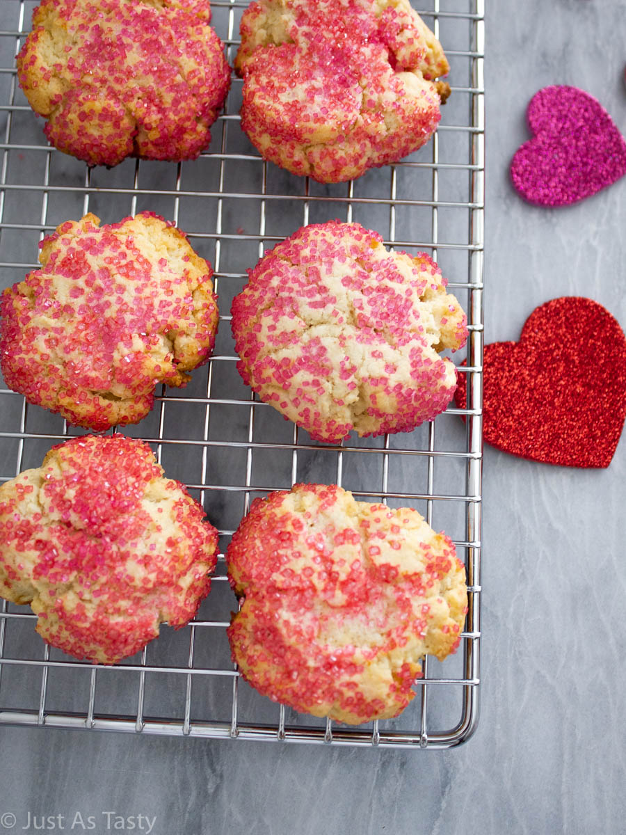 Cream cheese sugar cookies topped with pink sanding sugar on a wire cooling rack.