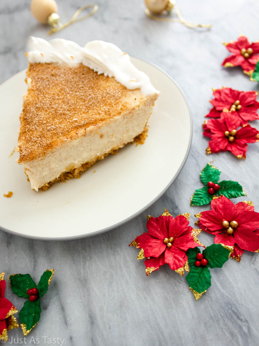 Slice of snickerdoodle cheesecake on a white plate surrounded by red flowers.