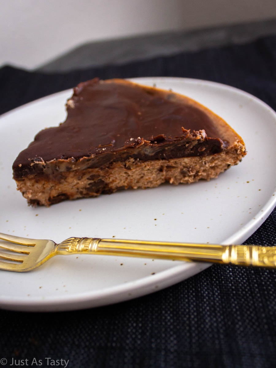 Slice of chocolate cheesecake on a white plate.