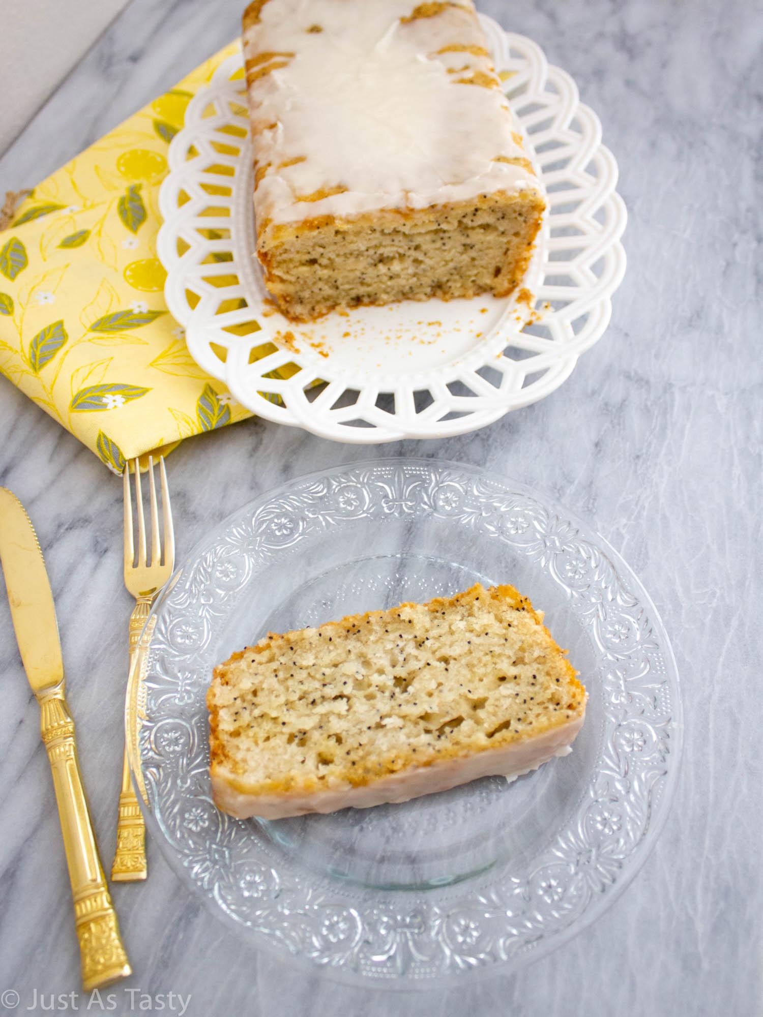 Slice of lemon poppy seed loaf on a glass plate.