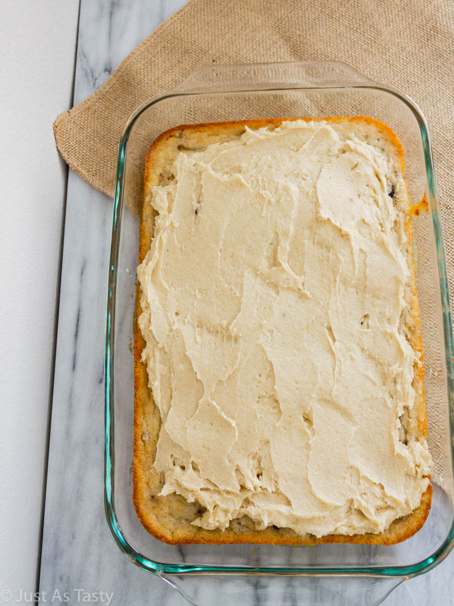 Frosted banana cake in a glass baking dish.