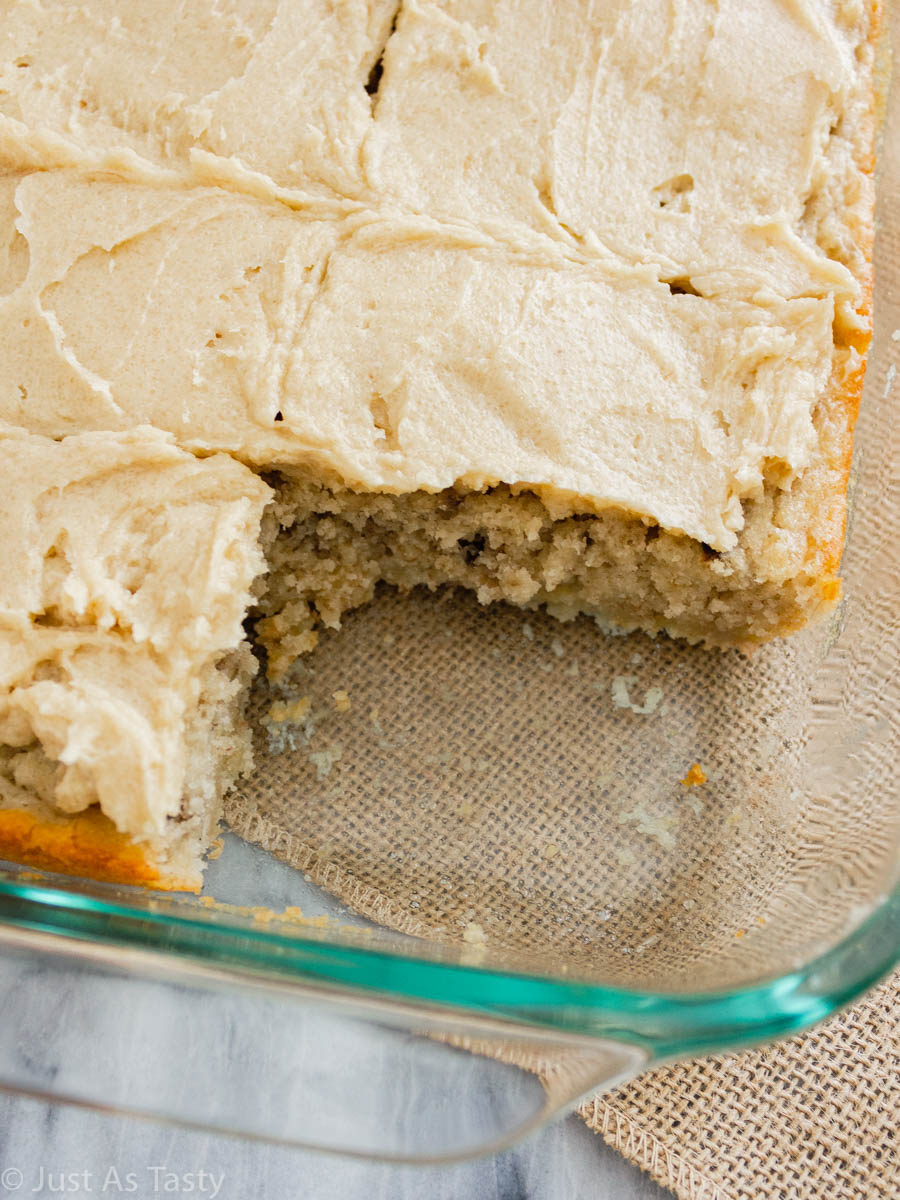 Frosted banana cake with a slice missing.