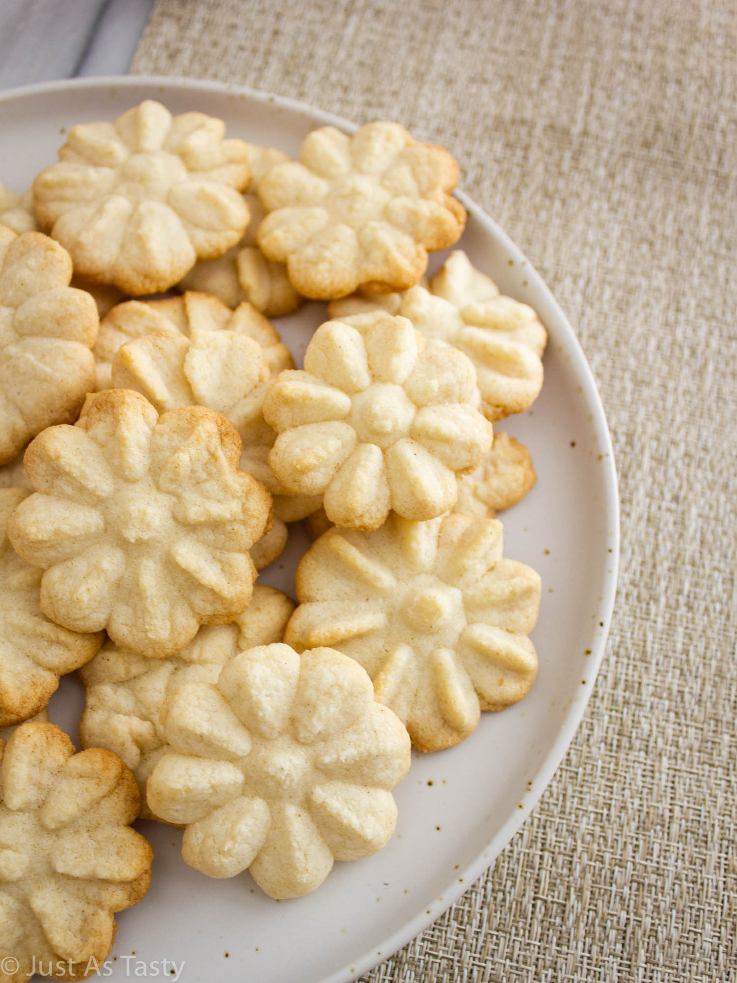 Plate full of flower-shaped buttery spritz cookies.