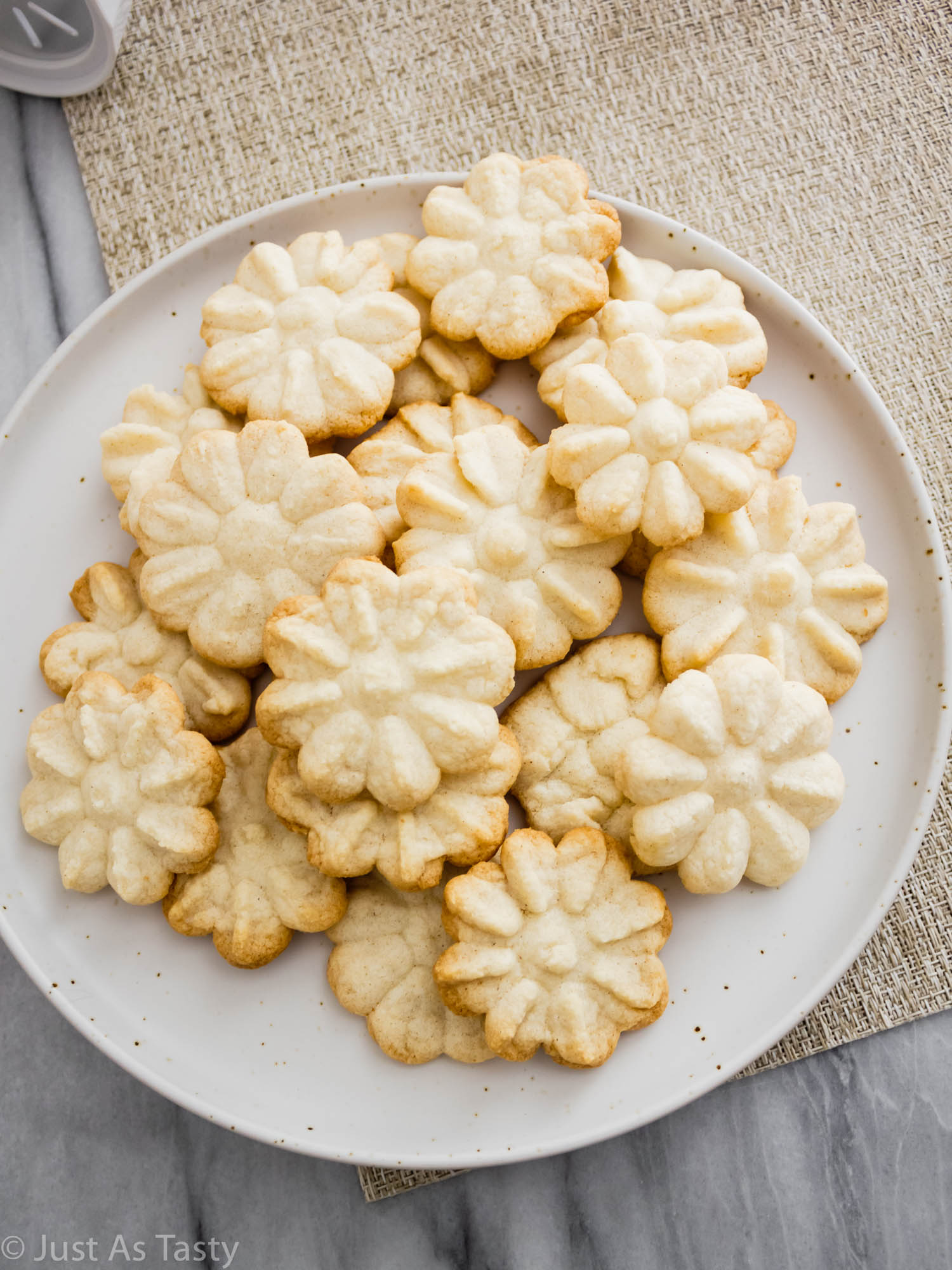 Plate full of flower shaped buttery spritz cookies.