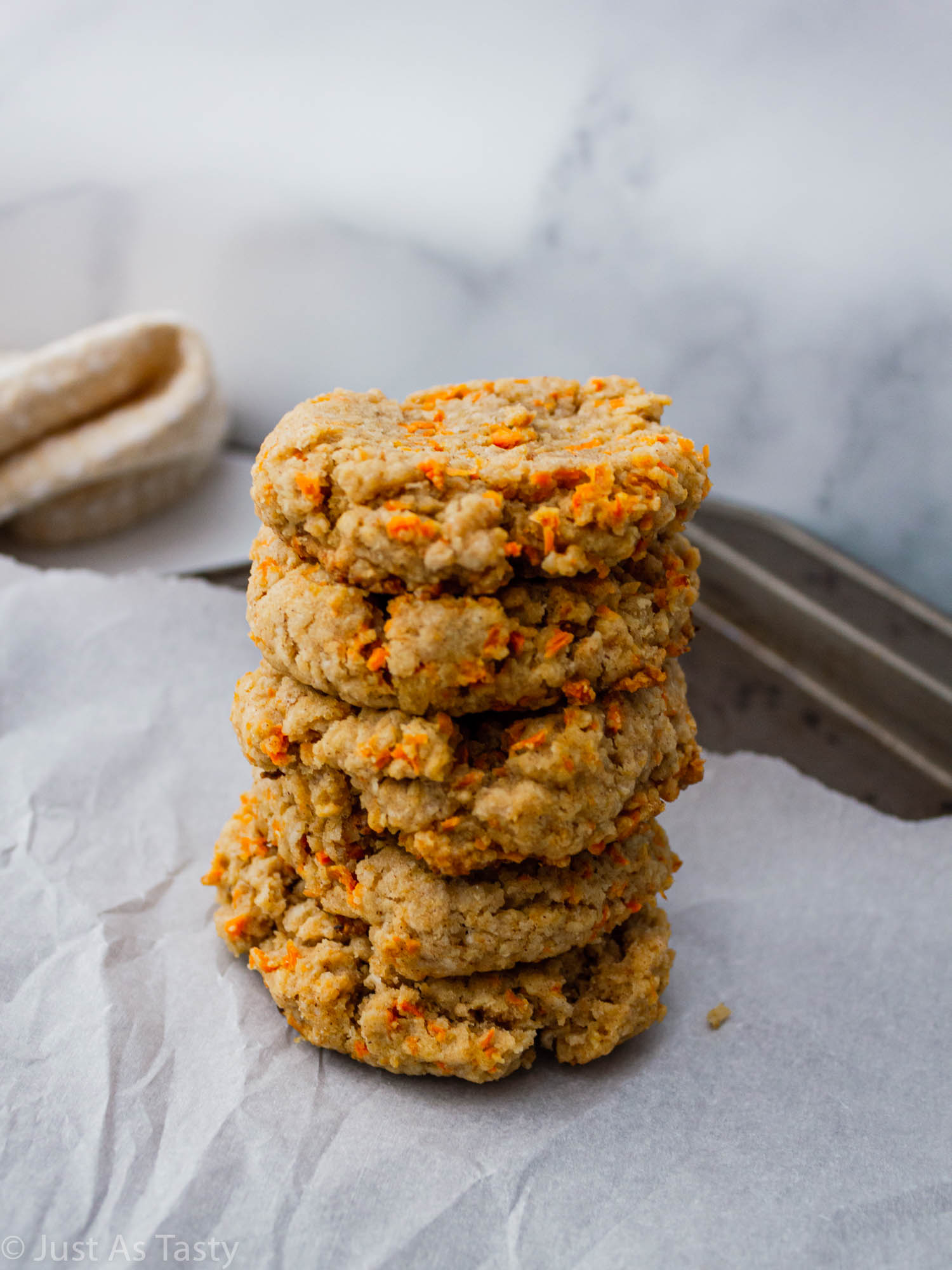 Stack of carrot cake cookies on parchment paper.