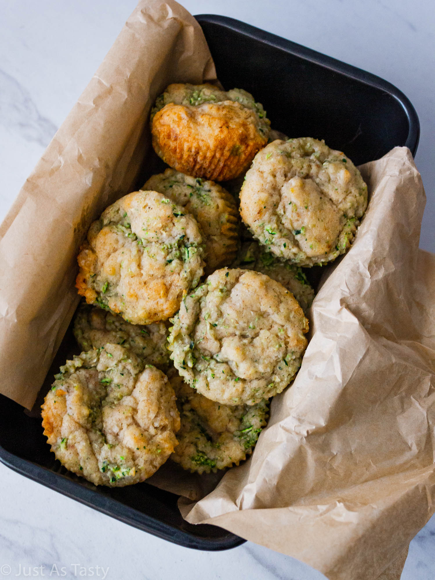 Zucchini muffins in a pan lined with parchment paper.
