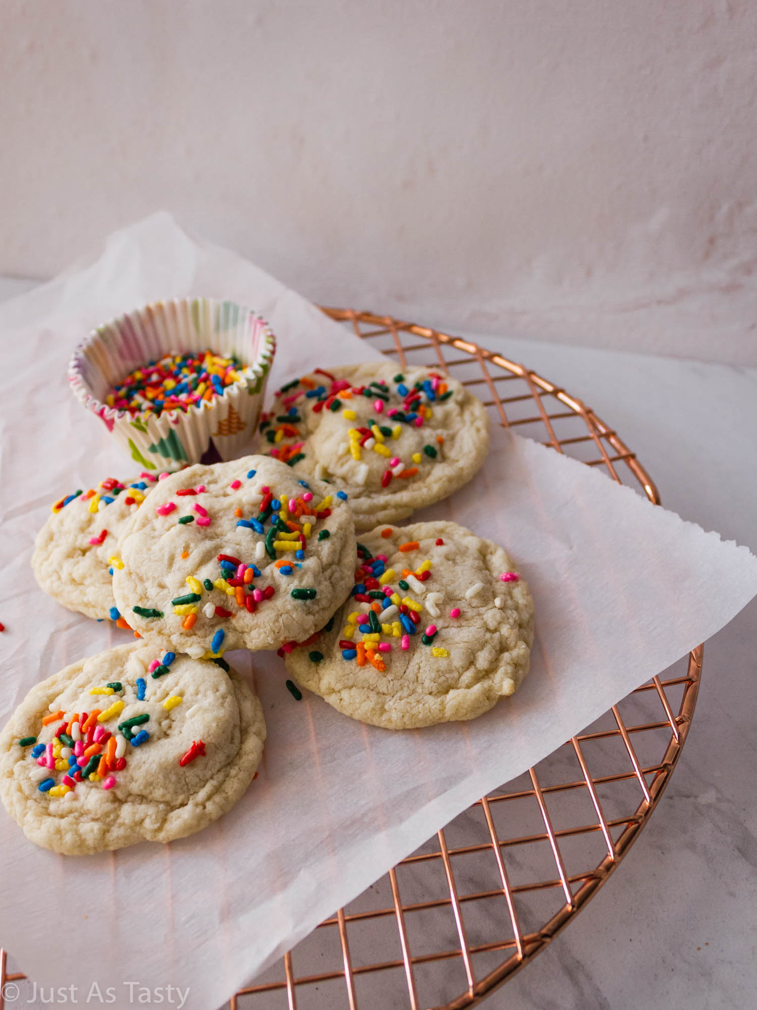Sugar cookies topped with rainbow sprinkles on parchment paper.