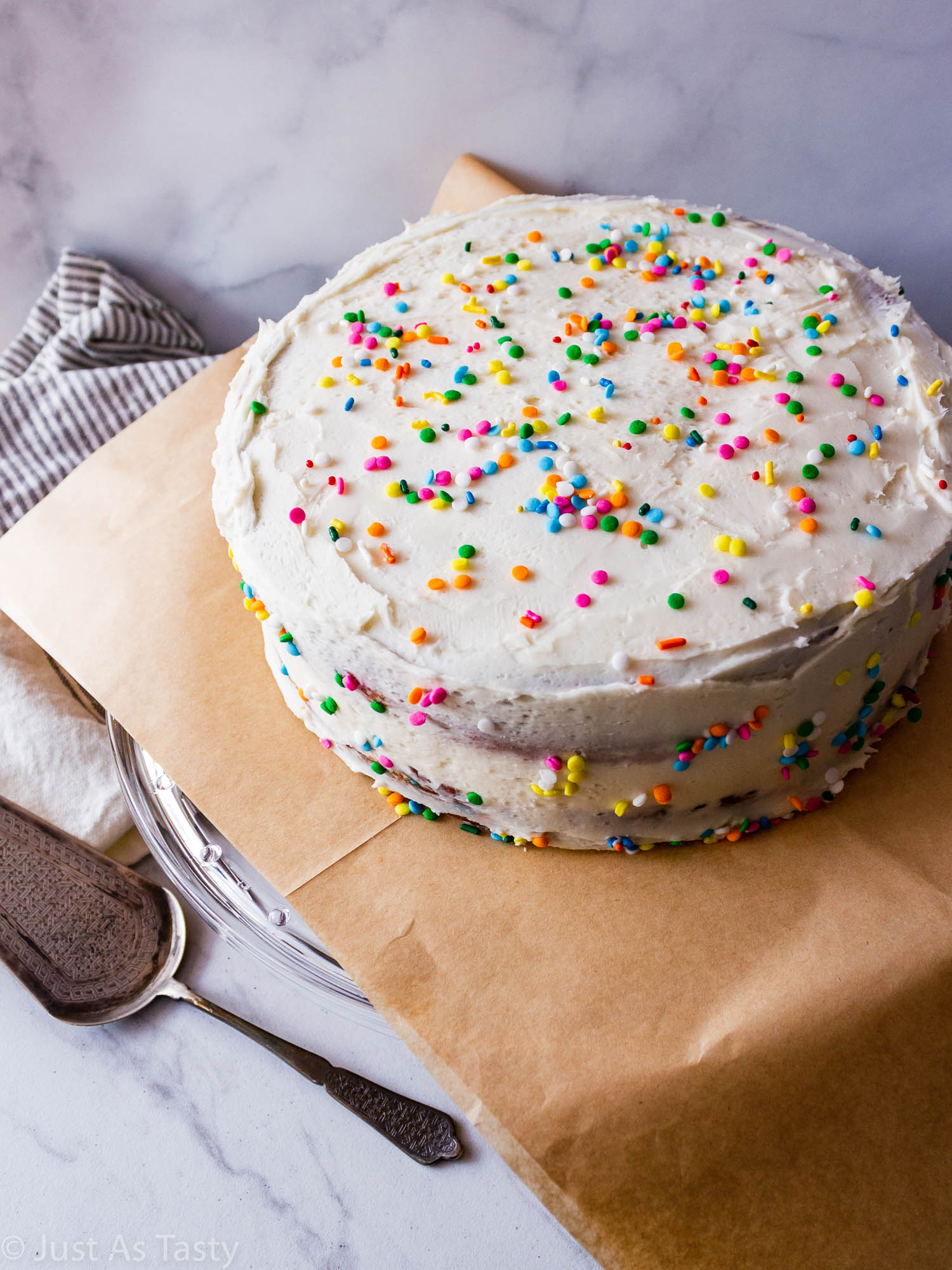 Frosted gluten free funfetti cake on a cake stand.