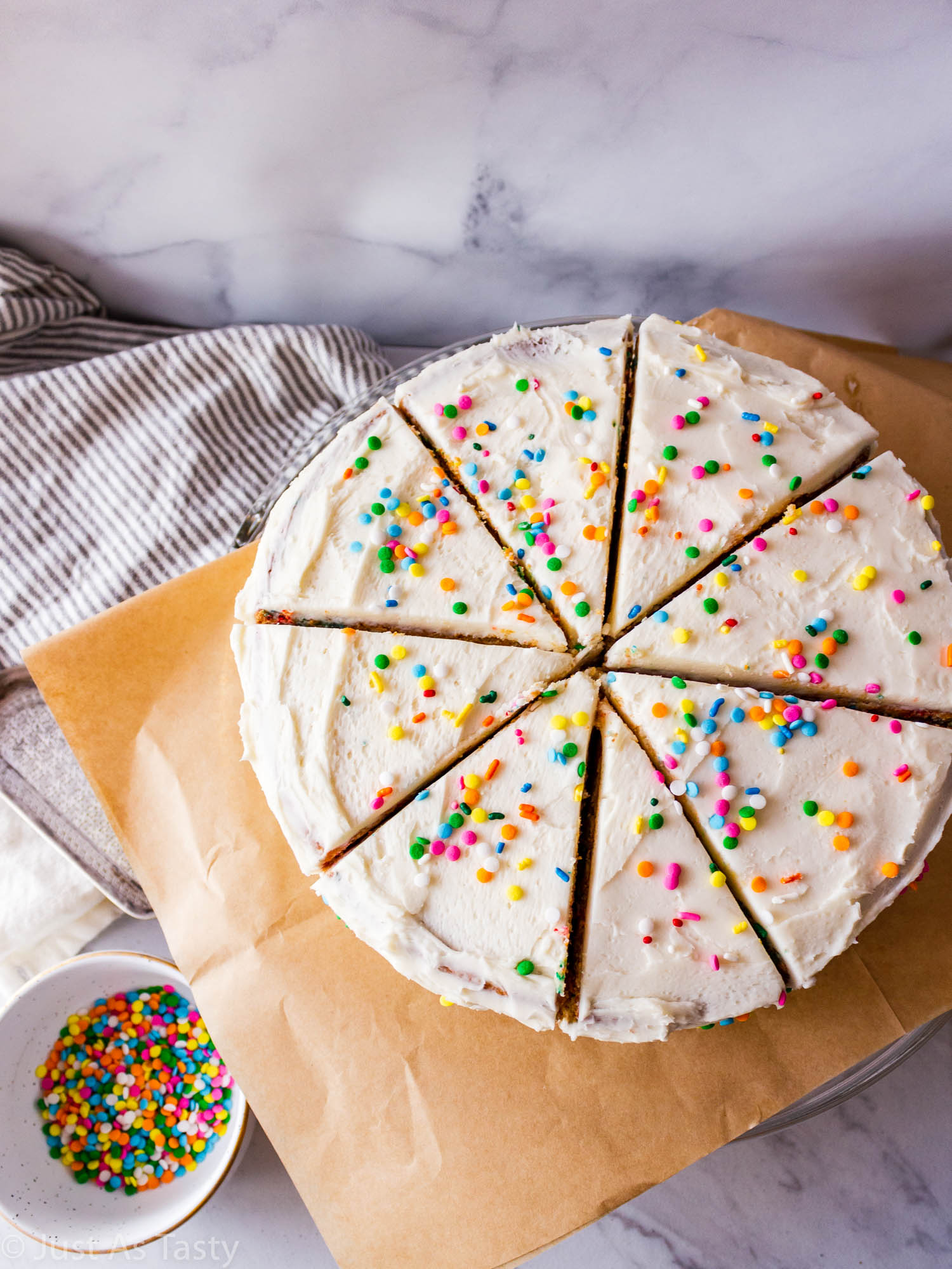 Frosted gluten free funfetti cake cut into slices.