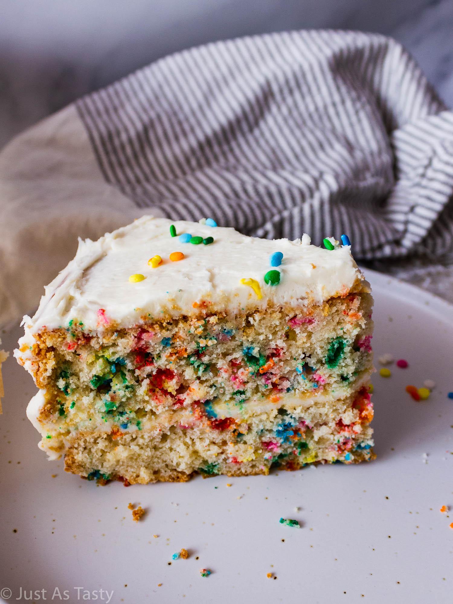 Slice of gluten free funfetti cake on a plate.