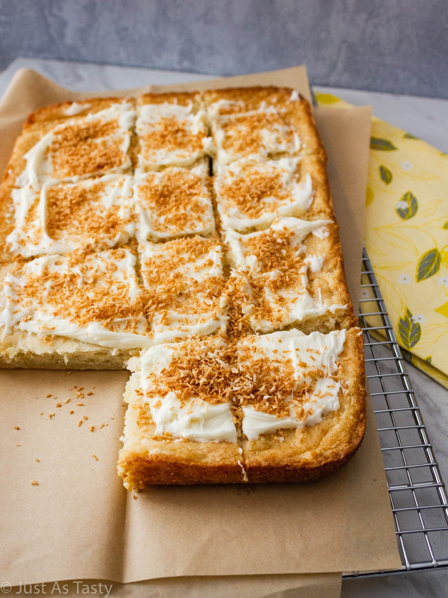 Frosted sheet cake topped with toasted coconut flakes.