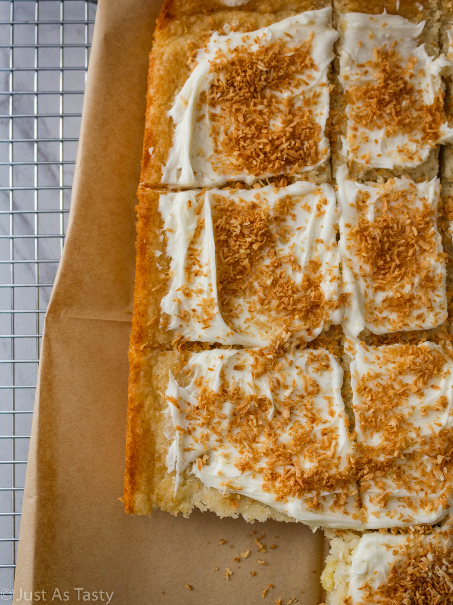 Frosted piña colada cake topped with toasted coconut flakes.