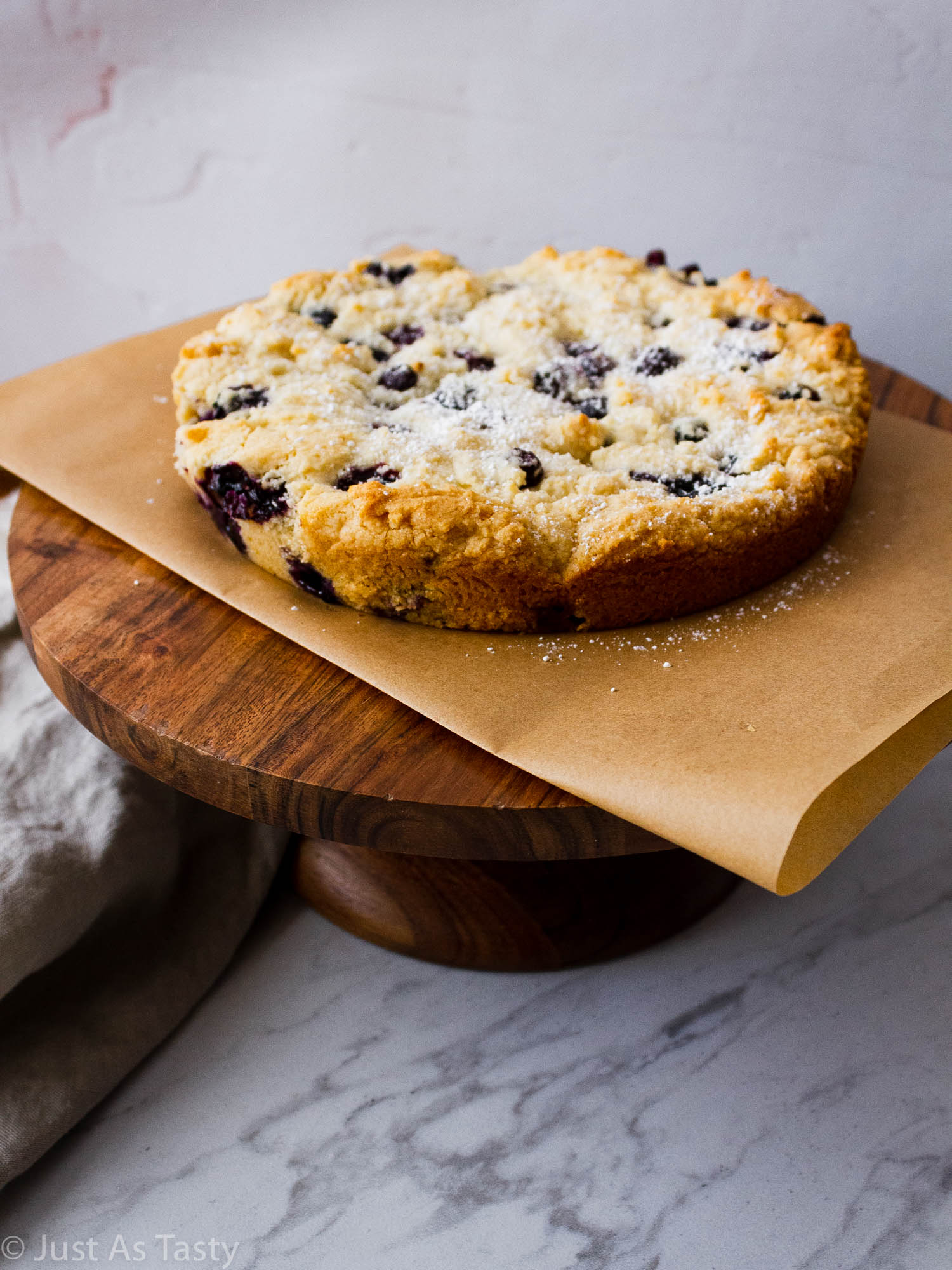 Gluten free blueberry cake on a cake stand.