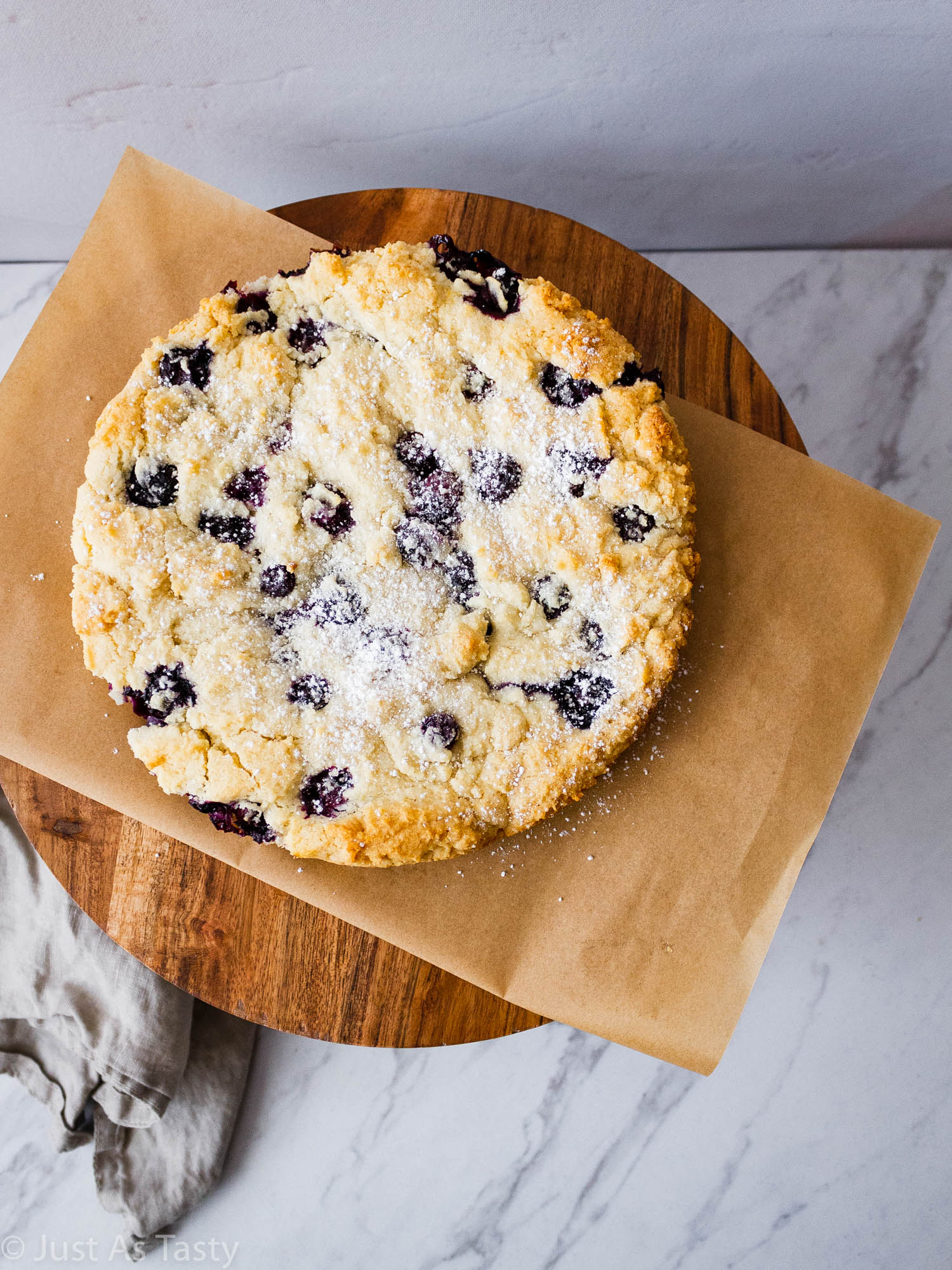 Round single layer blueberry cake on a cake stand.
