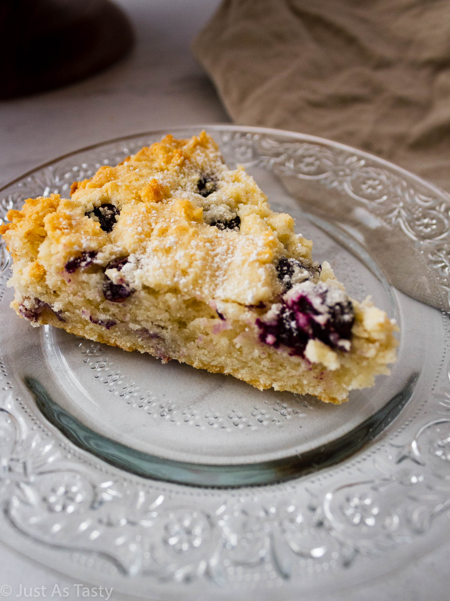 Slice of blueberry cake on a glass plate.