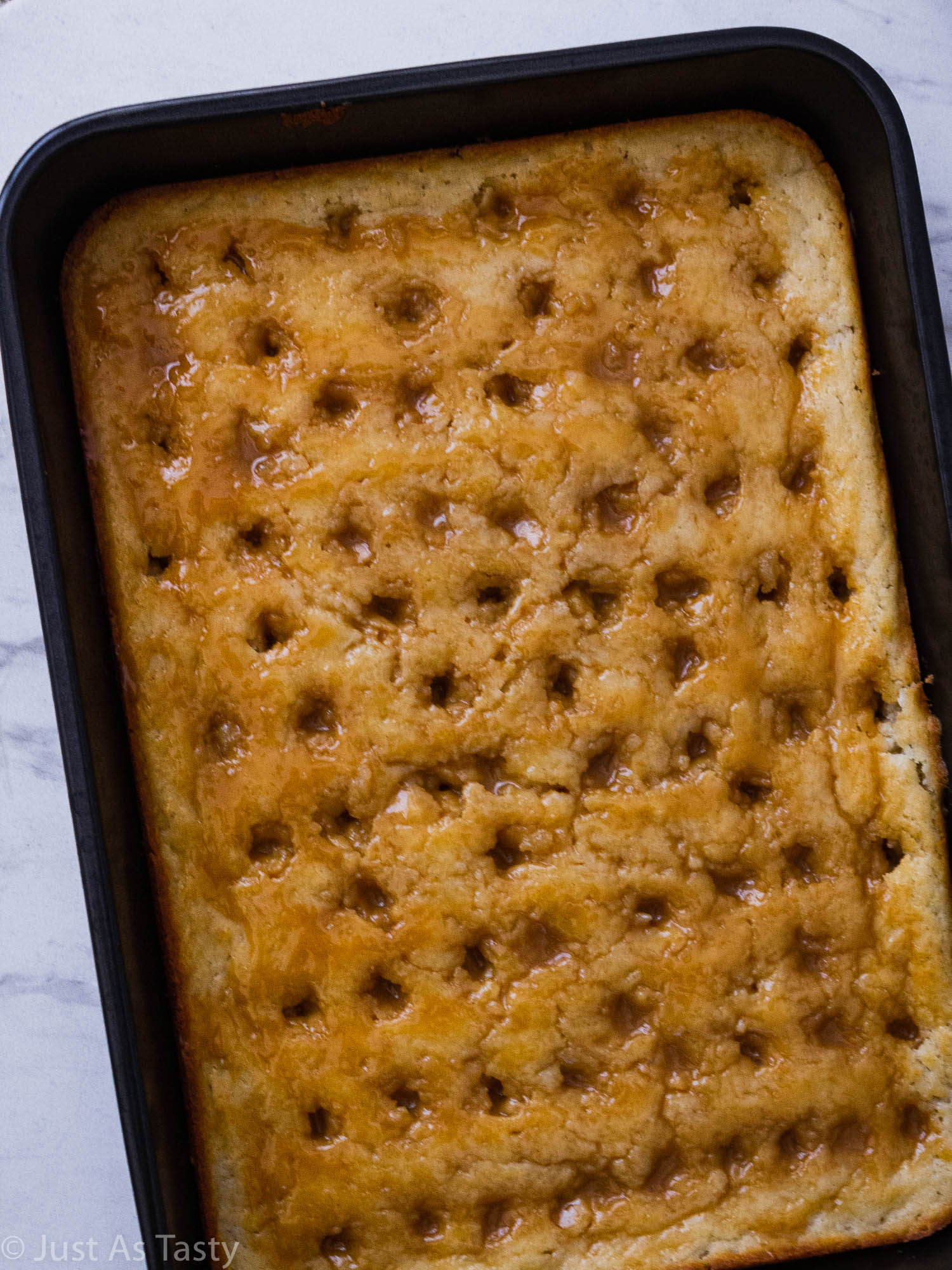 Sheet cake with holes poked all over surface and caramel sauce drizzled on top.