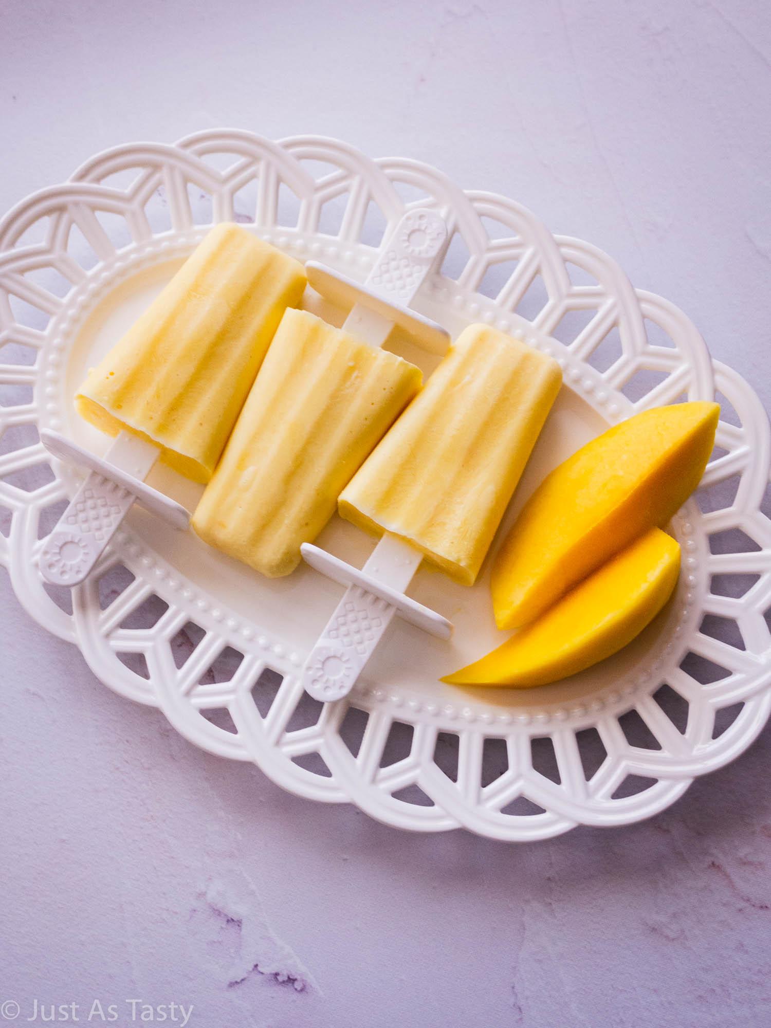 Three mango creamsicles on a white platter.
