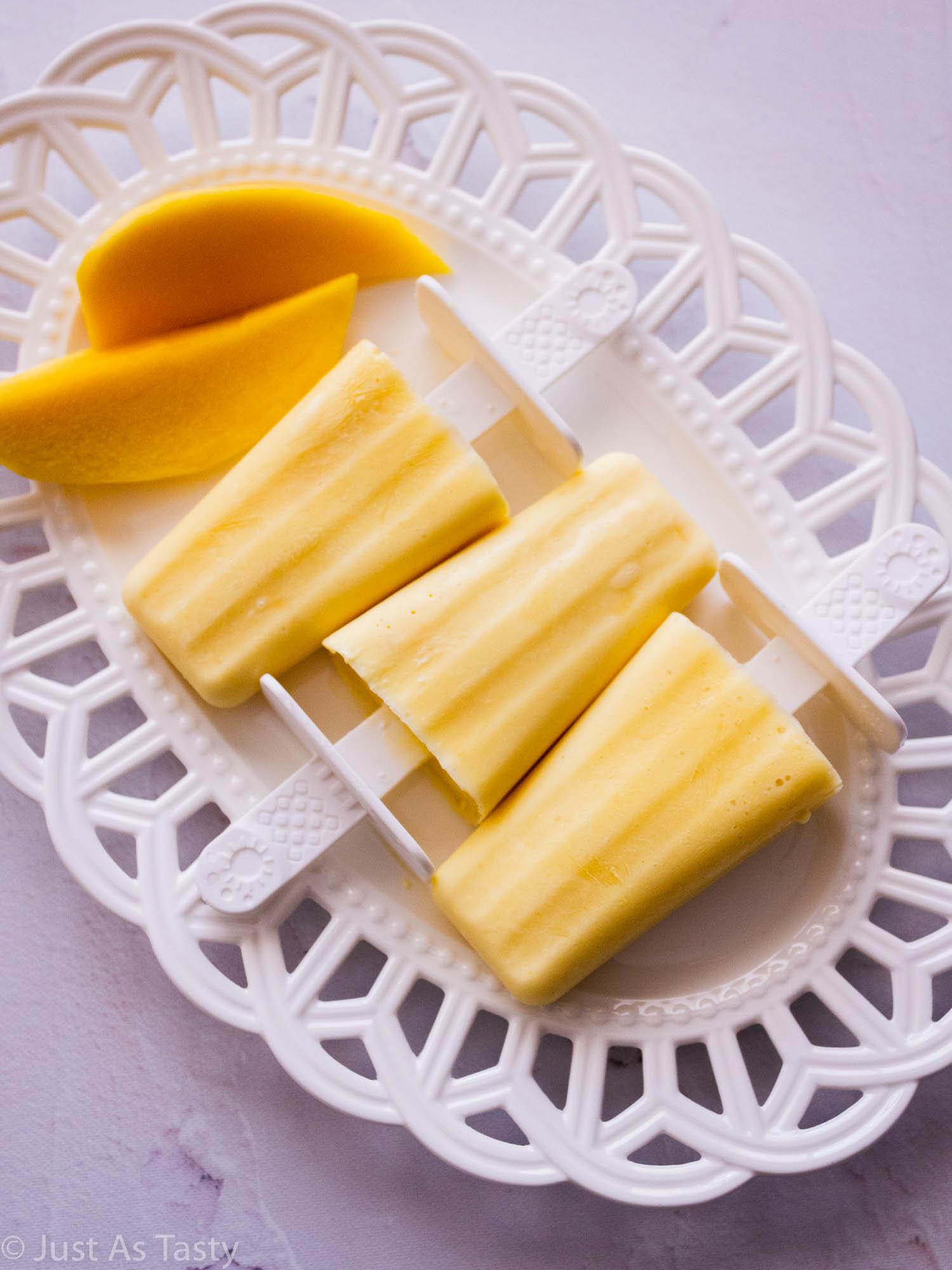 Mango creamsicles on a white platter.