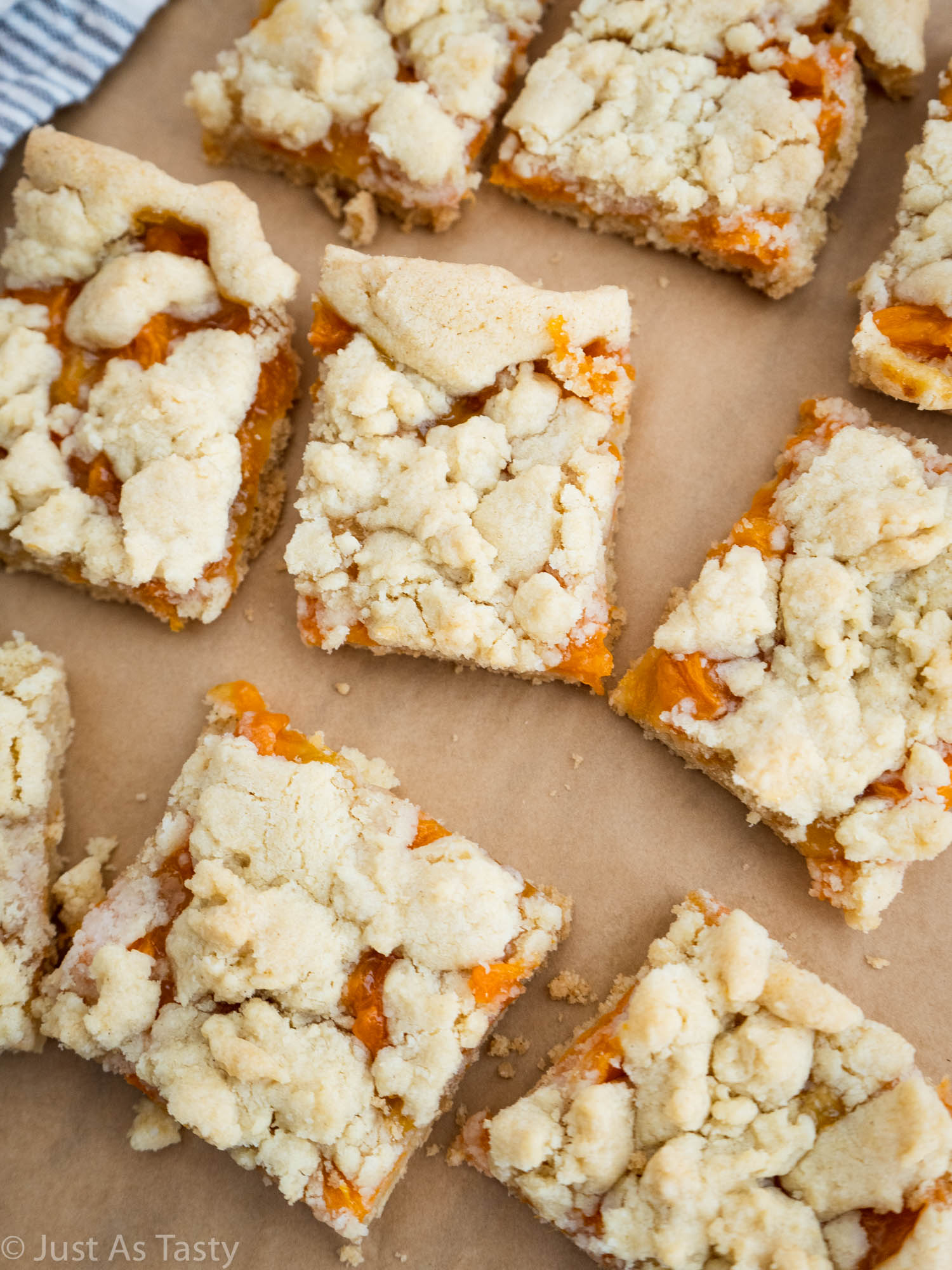 Apricot crumble bars on brown parchment paper.